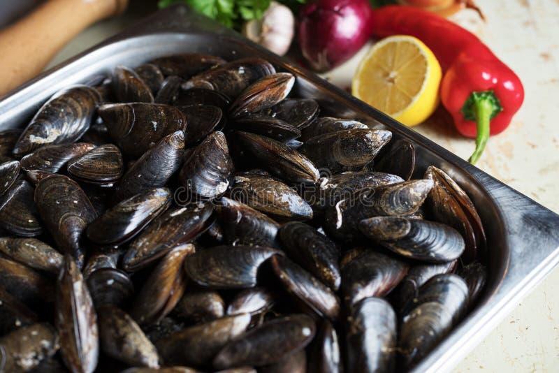 Mejillones frescos con los ingredientes para cocinar en el fondo rústico, visión superior, frontera Concepto de los mariscos imagenes de archivo
