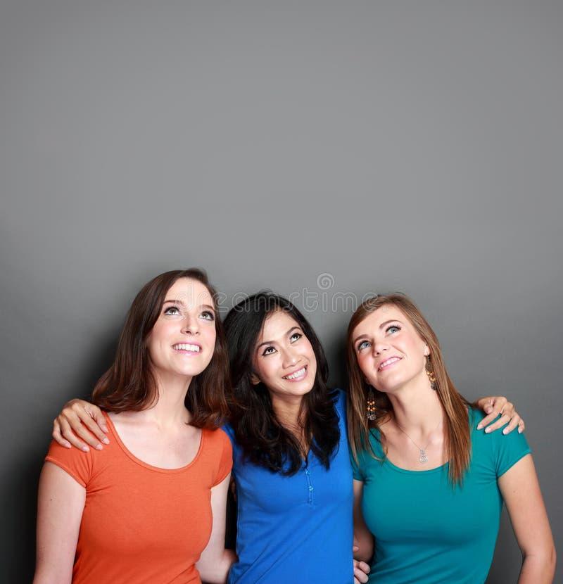 Mejor amigo de tres muchachas que mira para arriba al espacio en blanco imágenes de archivo libres de regalías