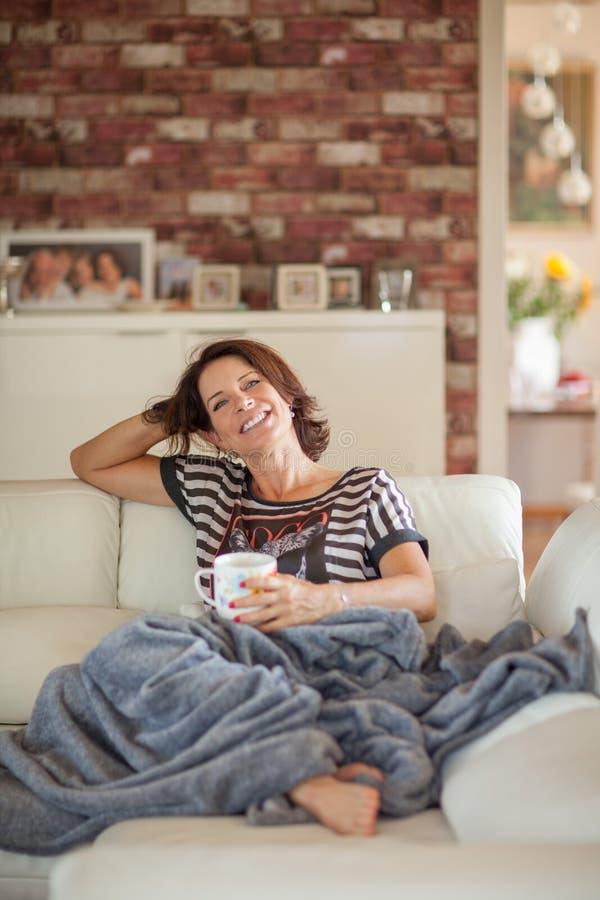 Mejor mujer hermosa de la edad que miente en la relajación del sofá, disfrutando de vida imágenes de archivo libres de regalías