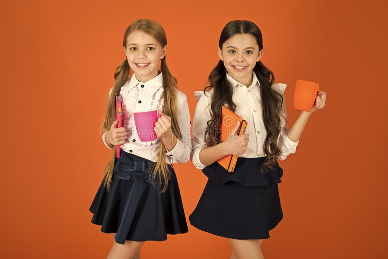 Mejora de su energ?a y humor Las peque?as muchachas gozan de las colegialas lindas del desayuno de la escuela que sostienen las t foto de archivo libre de regalías
