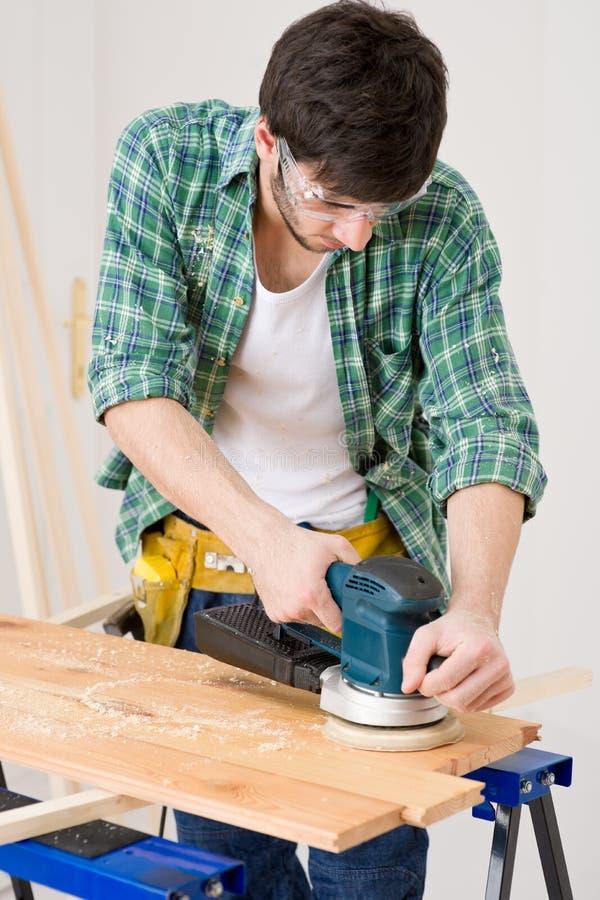 Mejoras para el hogar - manitas que enarena el suelo de madera imagenes de archivo