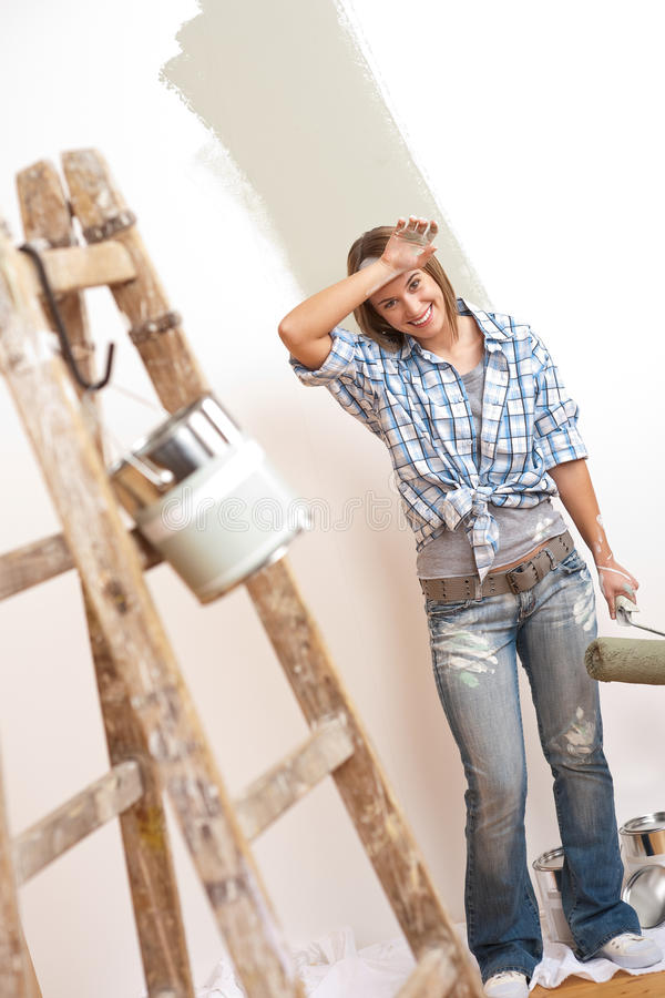 Mejoras para el hogar: Mujer alegre con el rodillo de pintura imagen de archivo