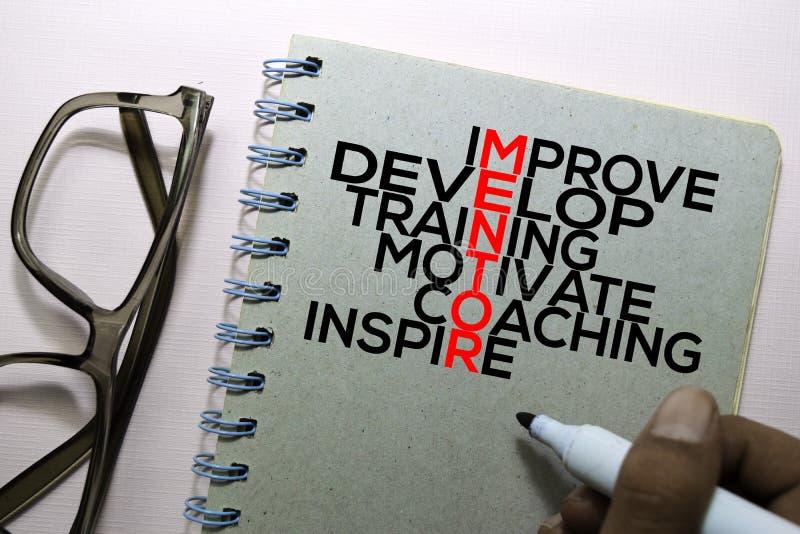 Mejore, conviértase, entrenamiento, motive, entrenando, inspire el texto del MENTOR en el libro aislado en el escritorio de ofici fotos de archivo