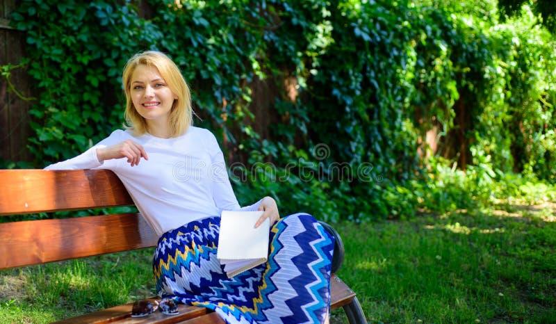 Mejore su conocimiento Rotura rubia sonriente feliz de la toma de la mujer que se relaja en libro de lectura del jardín La muchac fotografía de archivo libre de regalías