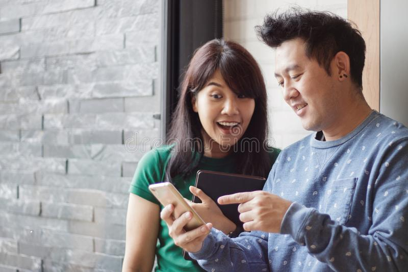 Mejores amigos alegres que ven las fotos divertidas en redes sociales vía el smartphone que se une Foco selectivo Copie el espaci foto de archivo libre de regalías