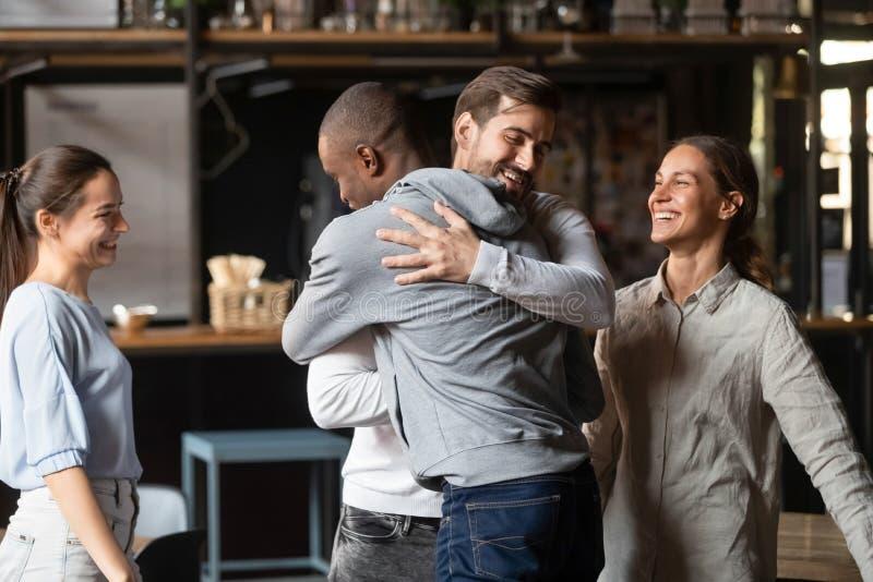 Mejores amigos diversos de los individuos que abrazan saludándose en el encuentro imagen de archivo
