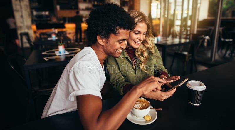 Mejores amigos en la cafetería que mira el teléfono elegante imagen de archivo libre de regalías