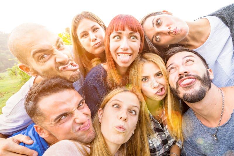 Mejores amigos felices que toman el selfie al aire libre con la iluminación trasera imagenes de archivo