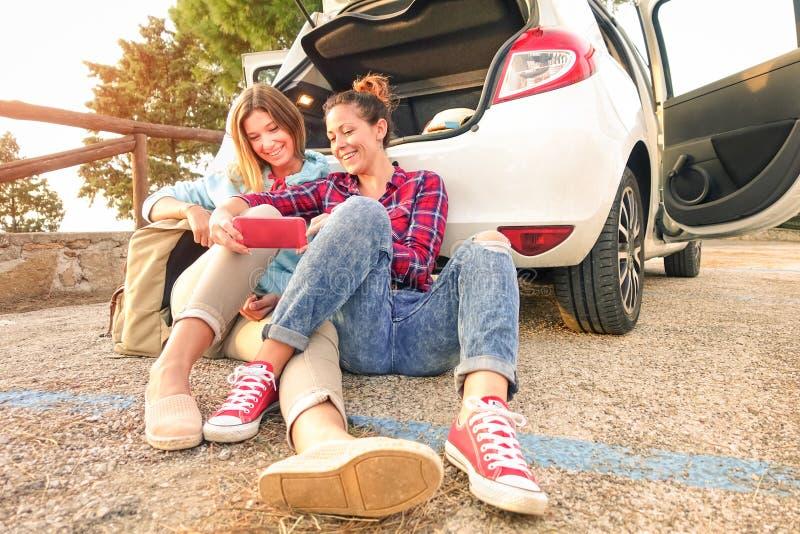 Mejores amigos femeninos jovenes que se divierten con el teléfono elegante móvil foto de archivo