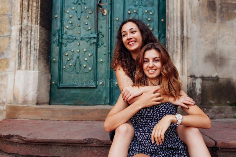 Mejores amigos femeninos jovenes que se sientan en las escaleras y el abrazo Muchachas felices que ríen y que se divierten imágenes de archivo libres de regalías