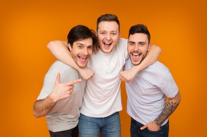 Mejores amigos Hombres que presentan sobre fondo anaranjado fotografía de archivo