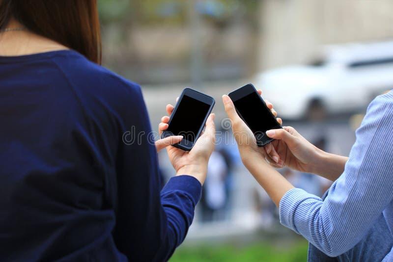 Mejores amigos, mujer que usa el artilugio electrónico, mensaje que mecanografía o comprobando newsfeed en redes sociales imagen de archivo libre de regalías