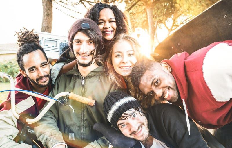 Mejores amigos multirraciales que toman el selfie en la competencia del parque del patín del bmx - concepto feliz de la juventud  fotos de archivo