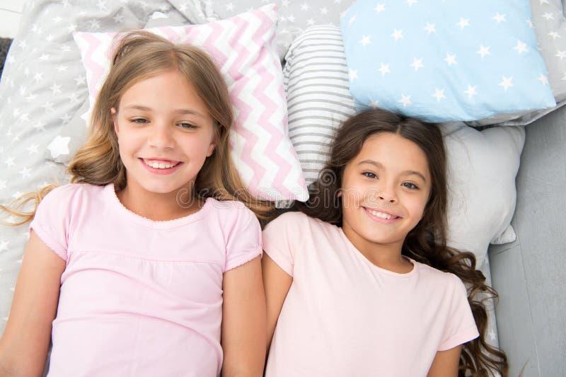 Mejores amigos por siempre Los niños de las muchachas mintieron en cama con la opinión superior de las almohadas lindas Concepto  foto de archivo