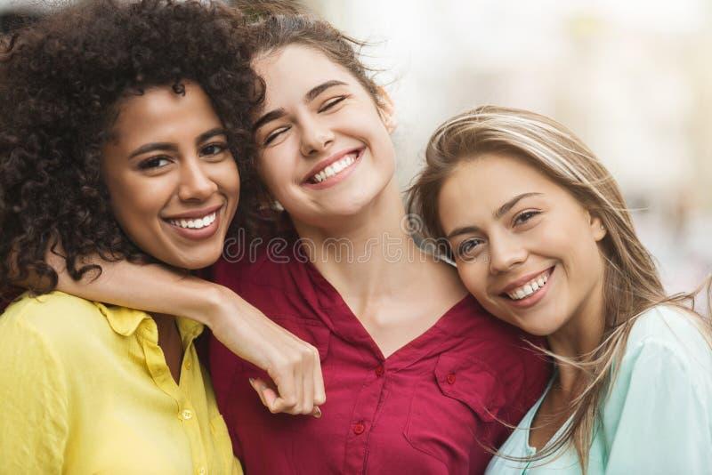 Mejores amigos que abrazan y que ríen en la calle imagen de archivo