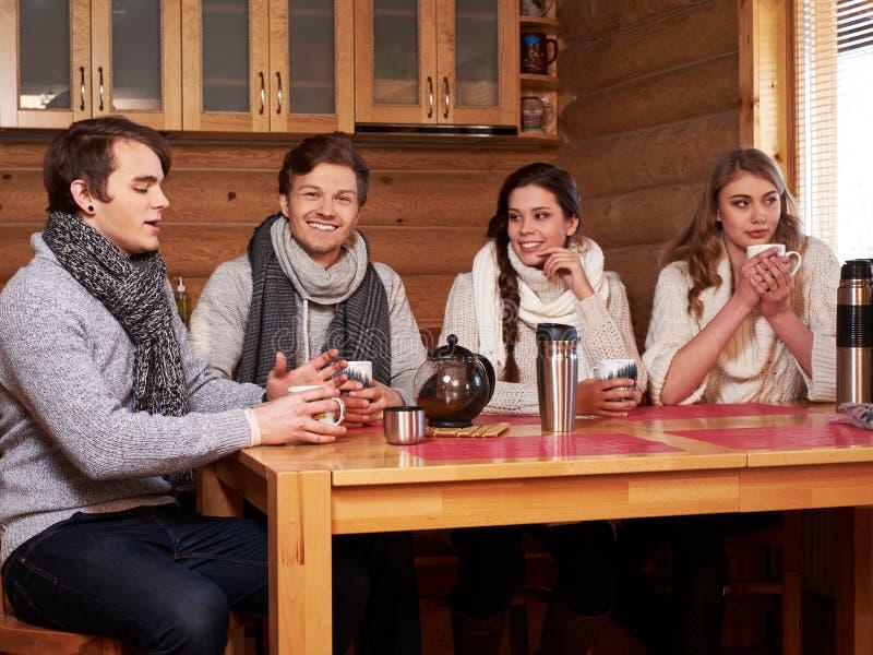 Mejores amigos que beben té caliente en cocina acogedora en la cabaña del invierno foto de archivo