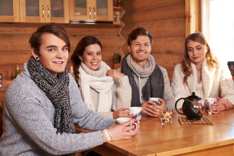 Mejores amigos que beben té caliente en cocina acogedora en la cabaña del invierno imagen de archivo libre de regalías