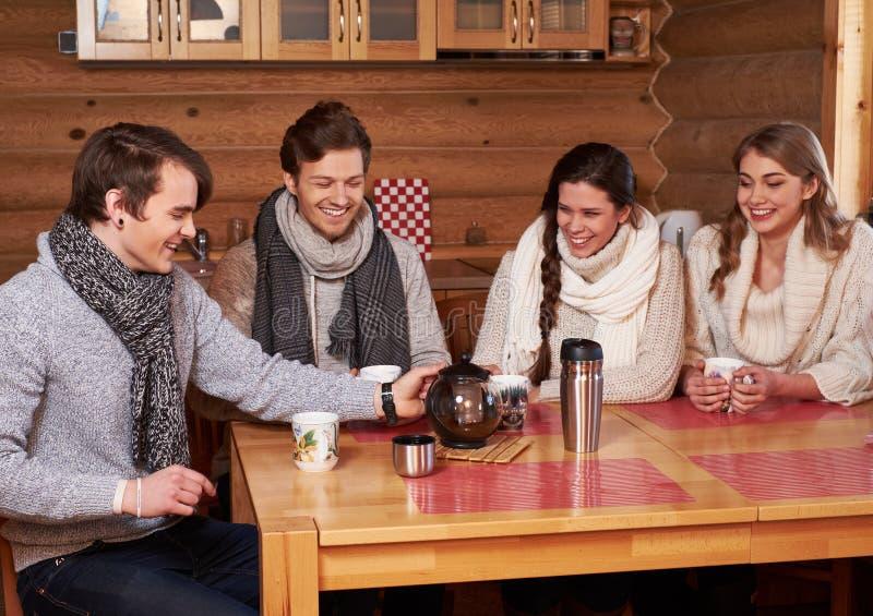 Mejores amigos que beben té caliente en cocina acogedora en la cabaña del invierno foto de archivo libre de regalías
