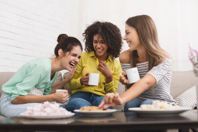 Mejores amigos que beben té y que hablan en casa foto de archivo