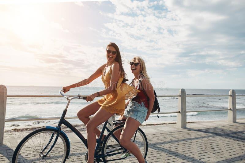 Mejores amigos que disfrutan de un paseo de la bici imagenes de archivo