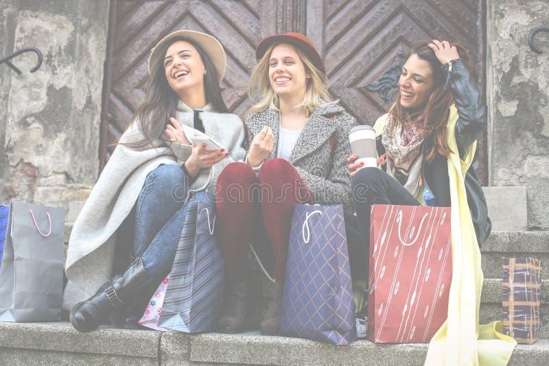 Mejores amigos que gozan después de hacer compras El sentarse de las chicas jóvenes imágenes de archivo libres de regalías