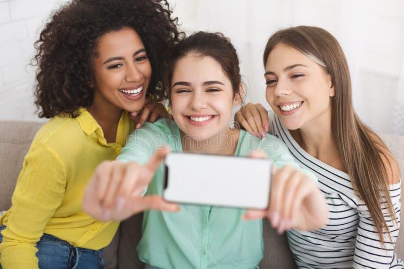 Mejores amigos que hacen las fotos en smartphone en casa fotos de archivo libres de regalías