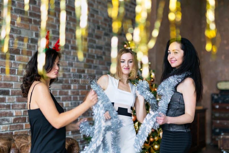 Mejores amigos que llevan los vestidos que bailan mientras que divirtiéndose en el partido del Año Nuevo fotos de archivo