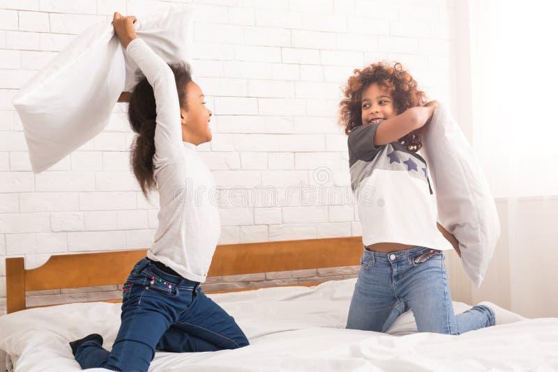 Mejores amigos que luchan con las almohadas, divirtiéndose imagen de archivo libre de regalías
