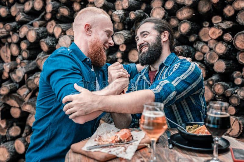 Mejores amigos que sacuden su mano mientras que se encuentra en el pub imagen de archivo