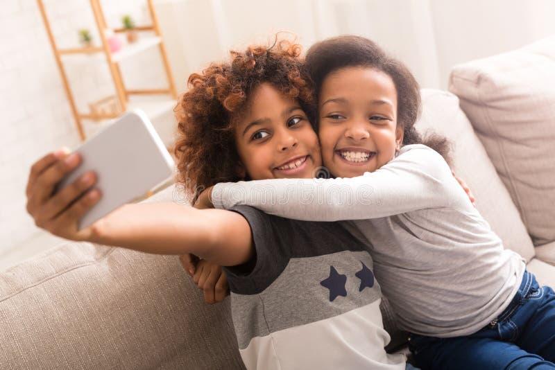 Mejores amigos que toman el selfie en smartphone en casa imagenes de archivo