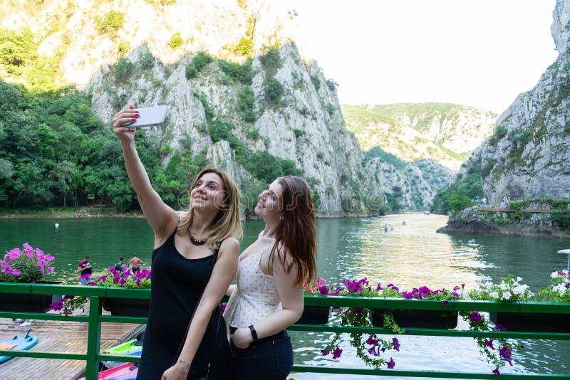 Mejores amigos que toman un selfie en un barranco con un teléfono celular y el sol en las montañas Dos cabezas caucásicas de las  imagen de archivo