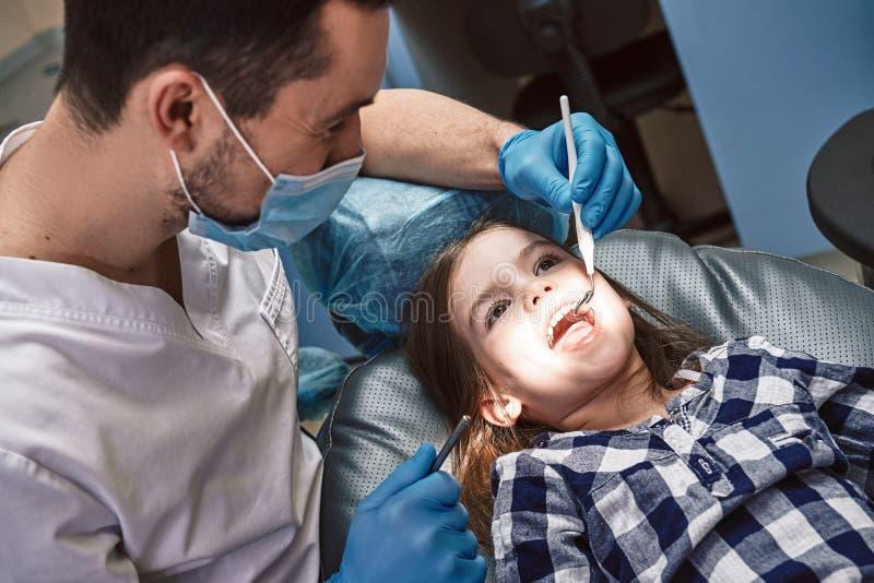 Mejores dientes, una mejor salud Ni?o en la oficina dental Dientes de examen del ` s de la ni?a del dentista en cl?nica imagen de archivo libre de regalías