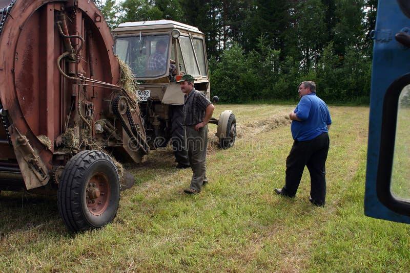 Mekaniker för traktorlantgårdutrustning kontrollerar i process av danandemummel royaltyfria bilder