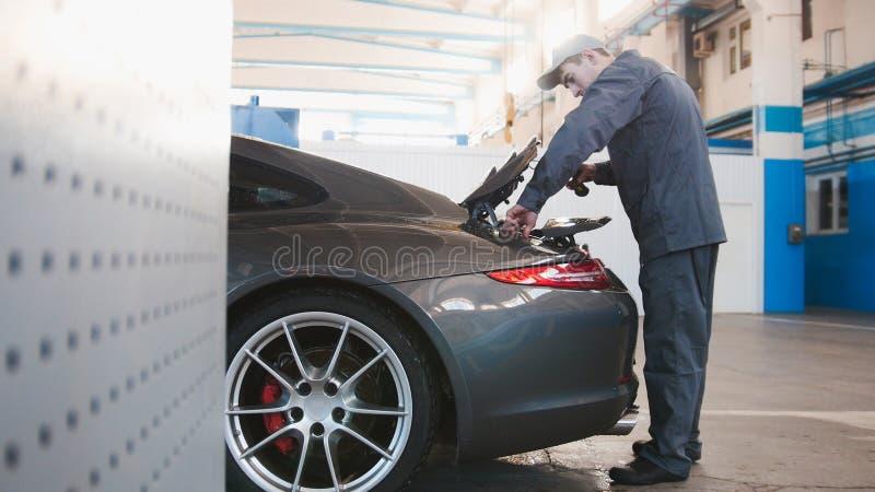 Mekaniker i bilgarage som kontrollerar huven för den lyxiga bilen royaltyfria foton