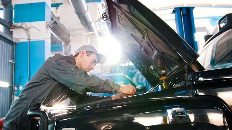 Mekaniker i bilservice - reparera i motorrummet för lyxiga SUV royaltyfria foton
