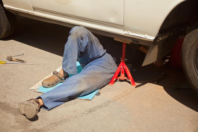 Mekaniker i den blåa smutsiga likformign som ner ligger och arbetar under bilen på automatiskservicegaraget royaltyfria bilder