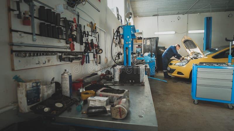 Mekaniker i garaget, bil som förbereder sig för att reparera, bred vinkel fotografering för bildbyråer