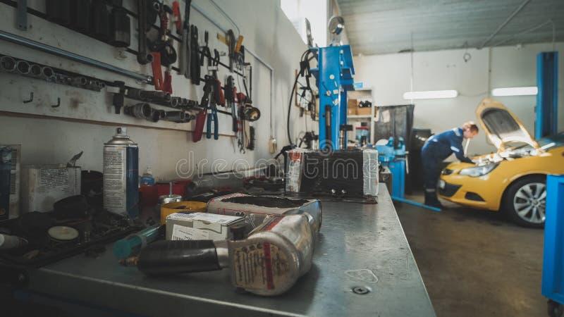 Mekaniker i garaget, bil som förbereder sig för att reparera, de-fokuserad bred vinkel - arkivbild