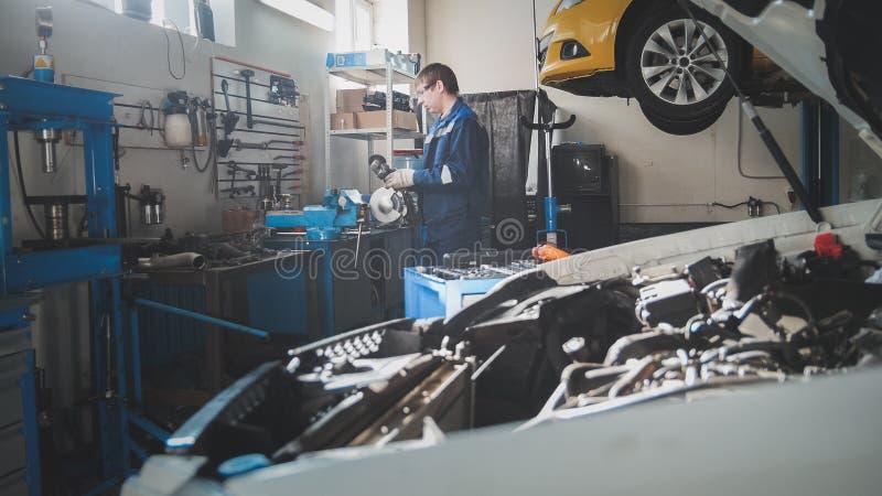 Mekaniker i garaget, bil som förbereder sig för yrkesmässig diagnostik arkivbilder