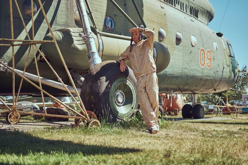 Mekaniker i likformig och flyg nära den stora militära helikoptern, medan luta på ett chassi i ett frilufts- museum arkivbilder
