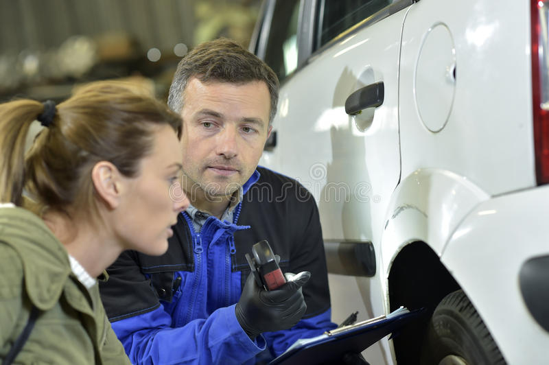 Mekaniker med försäkringsgivaren som beräknar bilskada arkivfoton