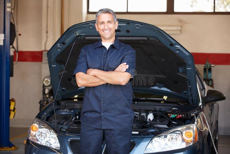 Mekaniker på arbete framme av bilen royaltyfri fotografi