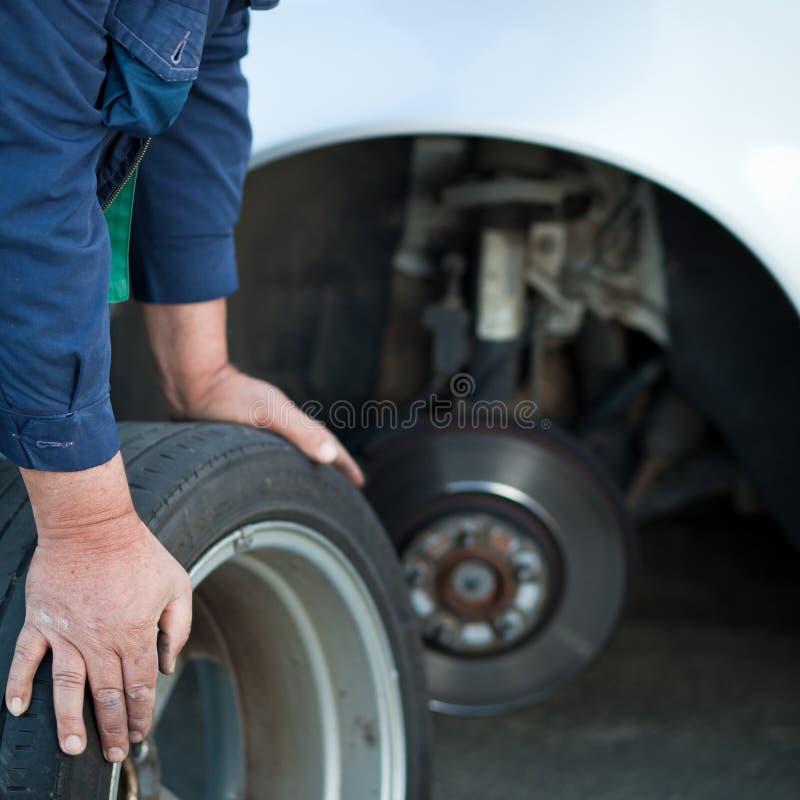 Mekaniker som ändrar ett hjul av en modern bil arkivfoton