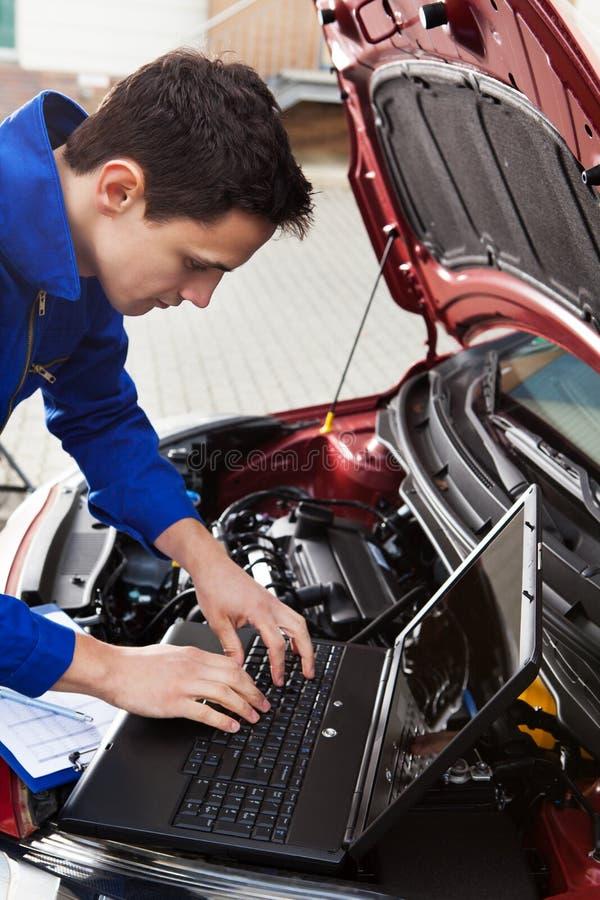 Mekaniker som använder bärbara datorn, medan reparera bilen royaltyfri fotografi