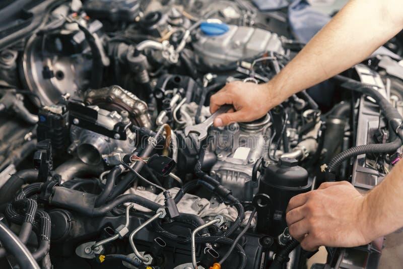 Mekaniker som arbetar på motorreparationer arkivfoto