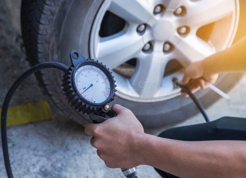 Mekaniker som blåser upp gummihjulet och kontrollerar lufttryck med måtttryck arkivfoto