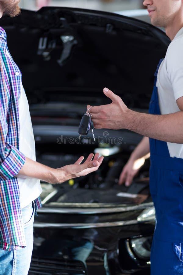 Mekaniker som ger biltangenter arkivbilder