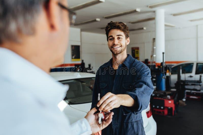 Mekaniker som ger biltangenter till kunden, når att ha servat arkivfoto