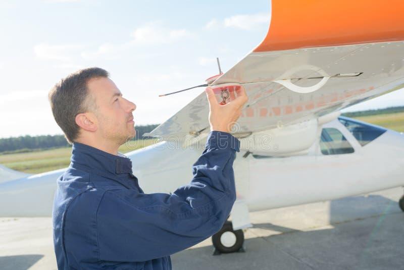 Mekaniker som kontrollerar vingflygplan royaltyfri fotografi
