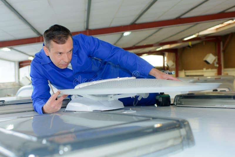 Mekaniker som passar den satellit- mottagaren för att taklägga campareskåpbilen arkivbild